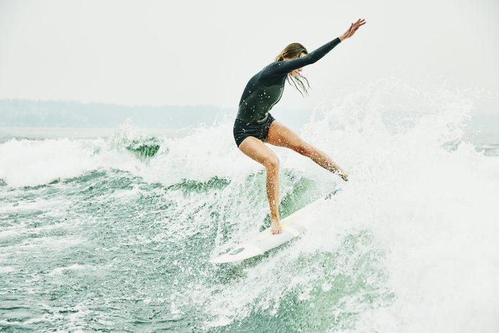 Female athlete wakesurfing during early morning session on lake