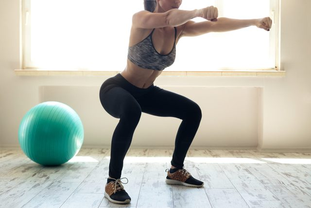 Woman in sportswear doing squat