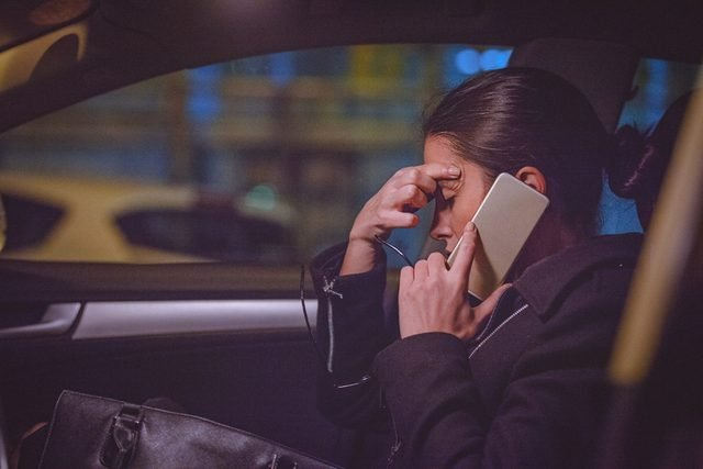 Young woman using smart phone on the front seat of the car at night
