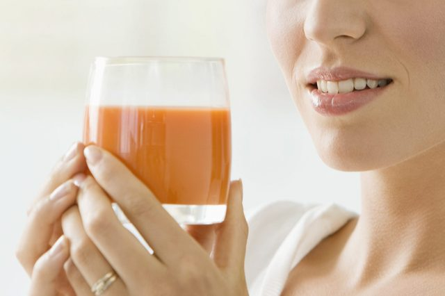 Woman holding a glass of tomato soup