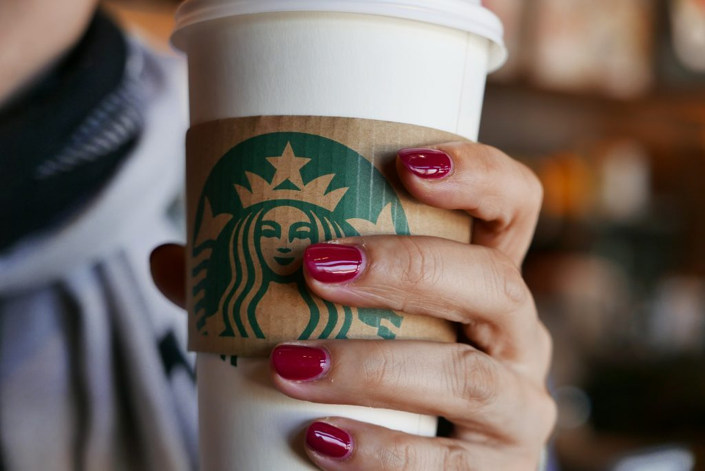Hand holding a coffee cup in a Starbucks coffee shop. In...