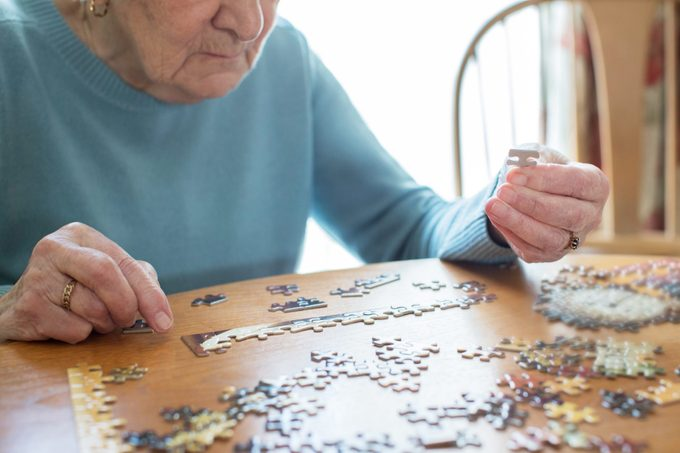 Close Up Of Senior Woman Relaxing With Jigsaw Puzzle At Home