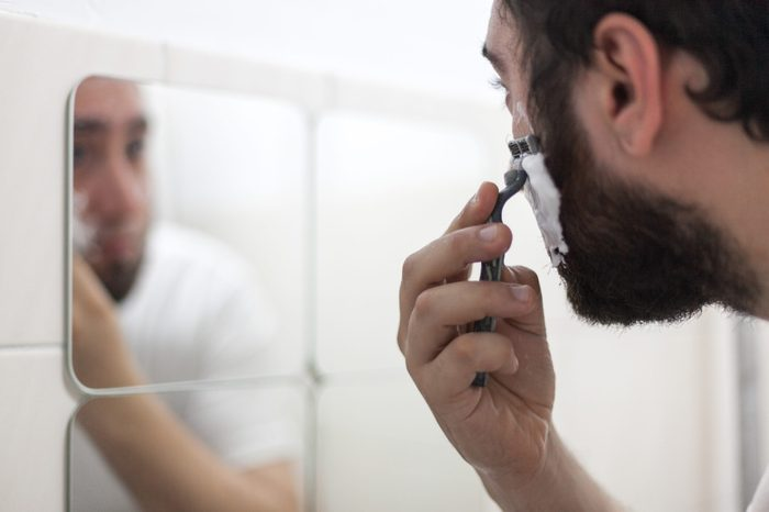 Man holding razor shaving face in front of mirror with foam on face