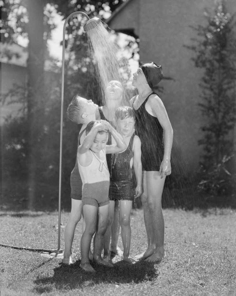 Children in bathing suits outside standing under a lawn shower, The May Company, Southern California, 1931.