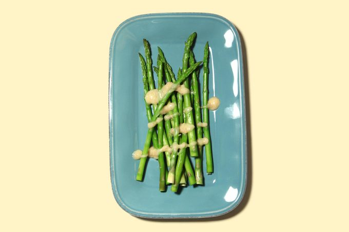 asparagus with buerre blanc on turquoise dish