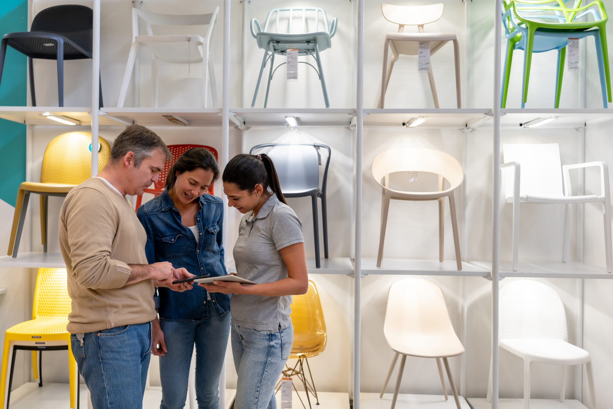 Friendly sales clerk helping adult couple look for furniture looking at a design on man's smartphone