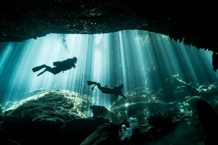 Scuba Divers and Light Rays in Eden Cenote