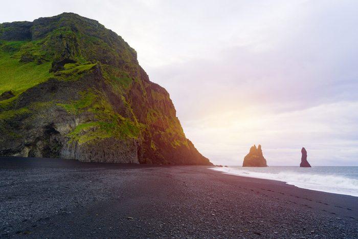 "Famous Basalt columns ""Troll toes"" at Reynisfjara black beach near Vik, Reynisdrangar, Southern Iceland. Coast of the Atlantic ocean. Solar bright gradient effect."