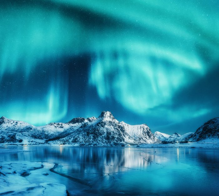 Aurora borealis above snowy mountains, frozen sea coast and reflection in water in Lofoten islands, Norway. Northern lights. Winter landscape with polar lights, ice in water. Sky with stars and aurora