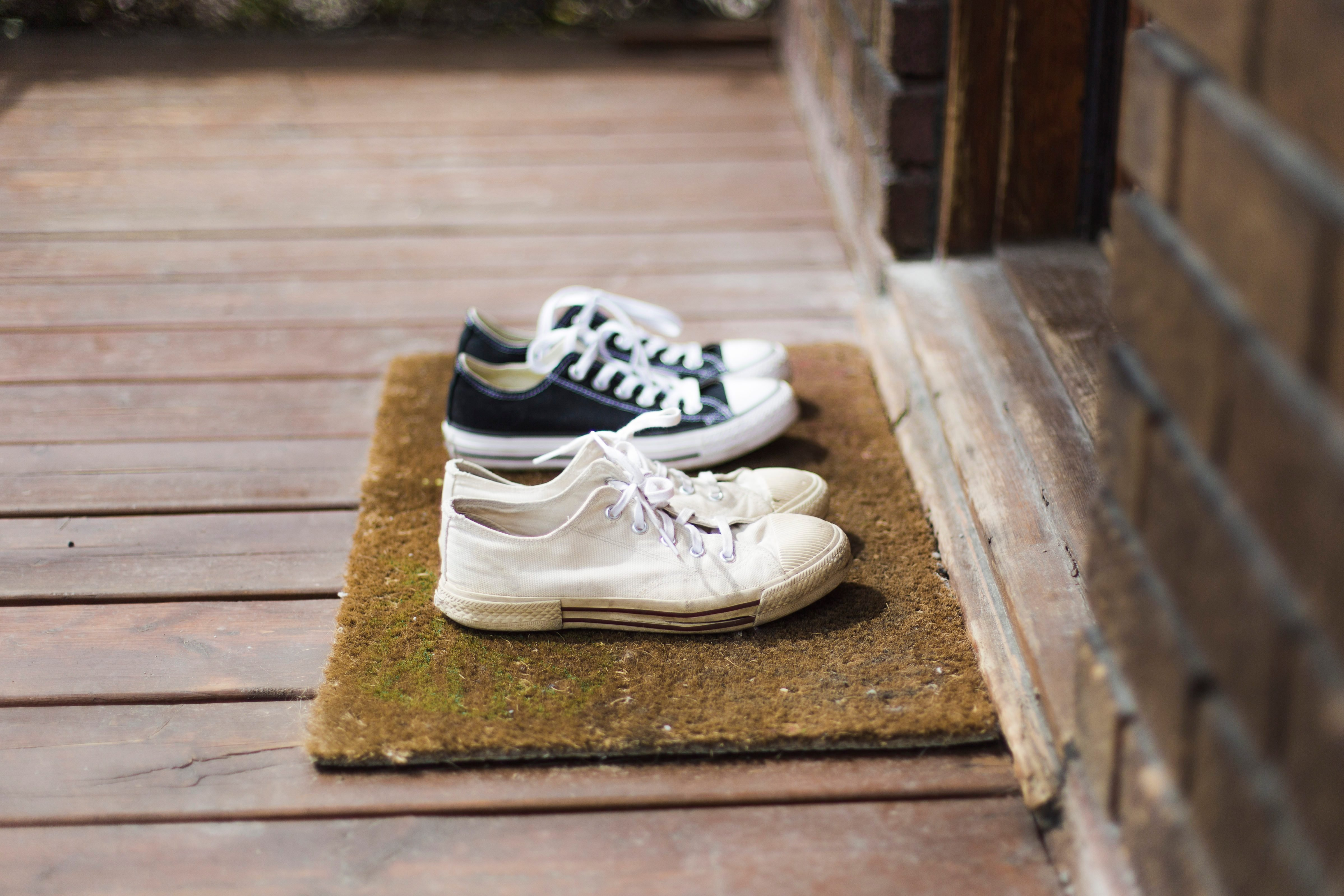 Home Moments - Two pair of black and white sneakers shoes on a porch
