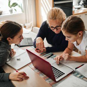 Homeschooling - Mother Helping To Her Daughters To Finish School Homework During Coronavirus Quarantine