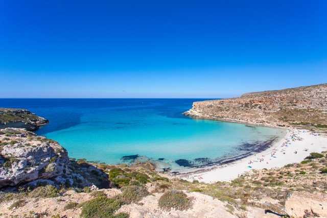 """Lampedusa Island Sicily - Rabbit Beach and Rabbit Island Lampedusa """"Spiaggia dei Conigli"""" with turquoise water and white sand at paradise beach. Mediterranean scrub with thyme and cardoon. Tabaccara Bay"""