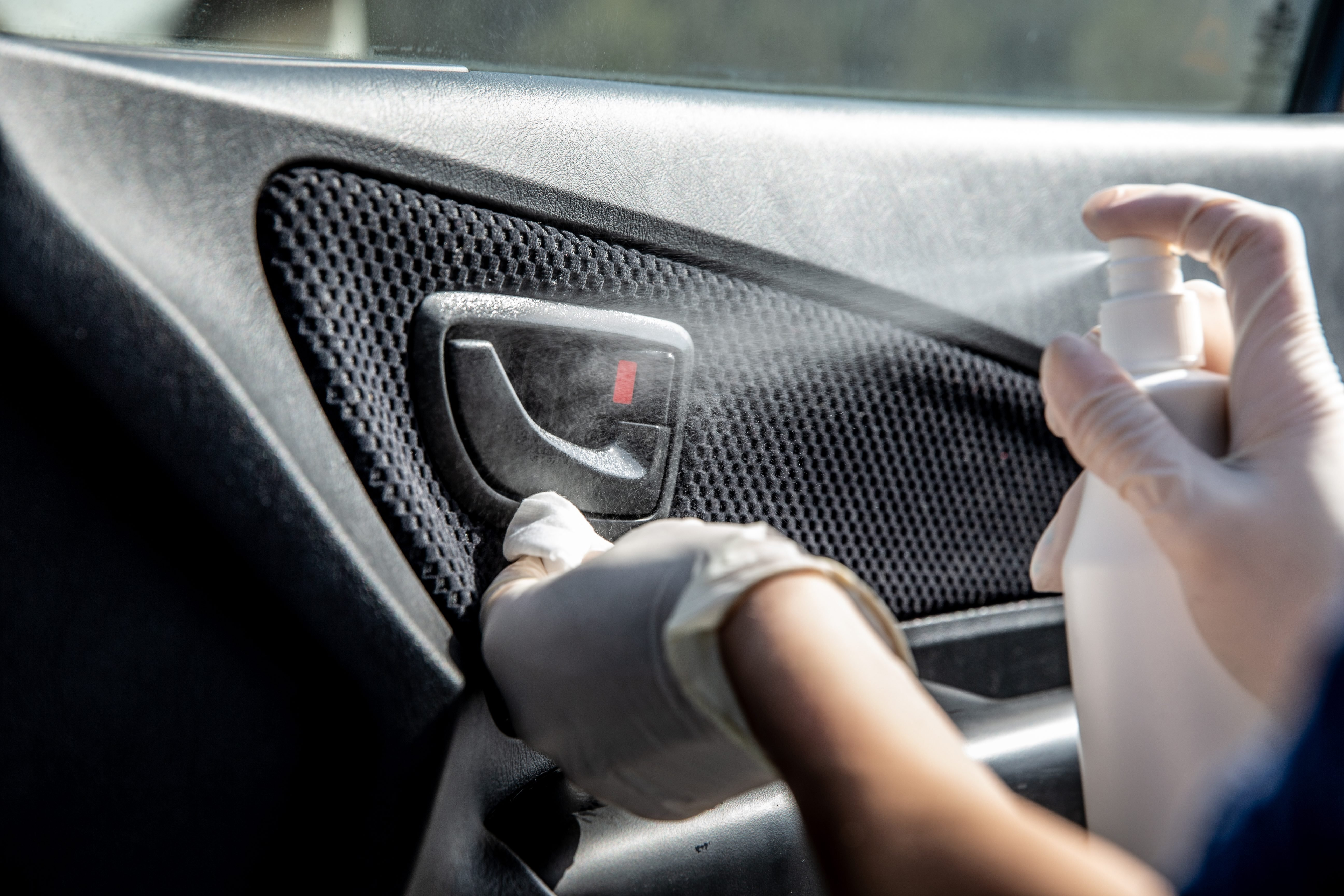 Woman Wearing Protective Gloves Cleaning Car Door Handle with Hand Sanitizer - stock photo