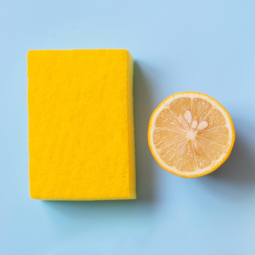 Flat lay composition with cleaning supplies, lemons and flower, bright concept of household chores