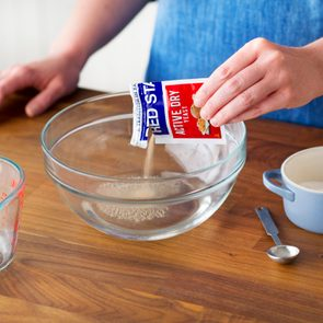 Person pouring an open packet of yeast into sugar and water inside a glass bowl