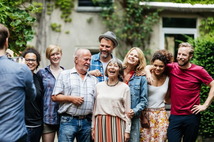 Man Taking Group Photo Of Family At BBQ
