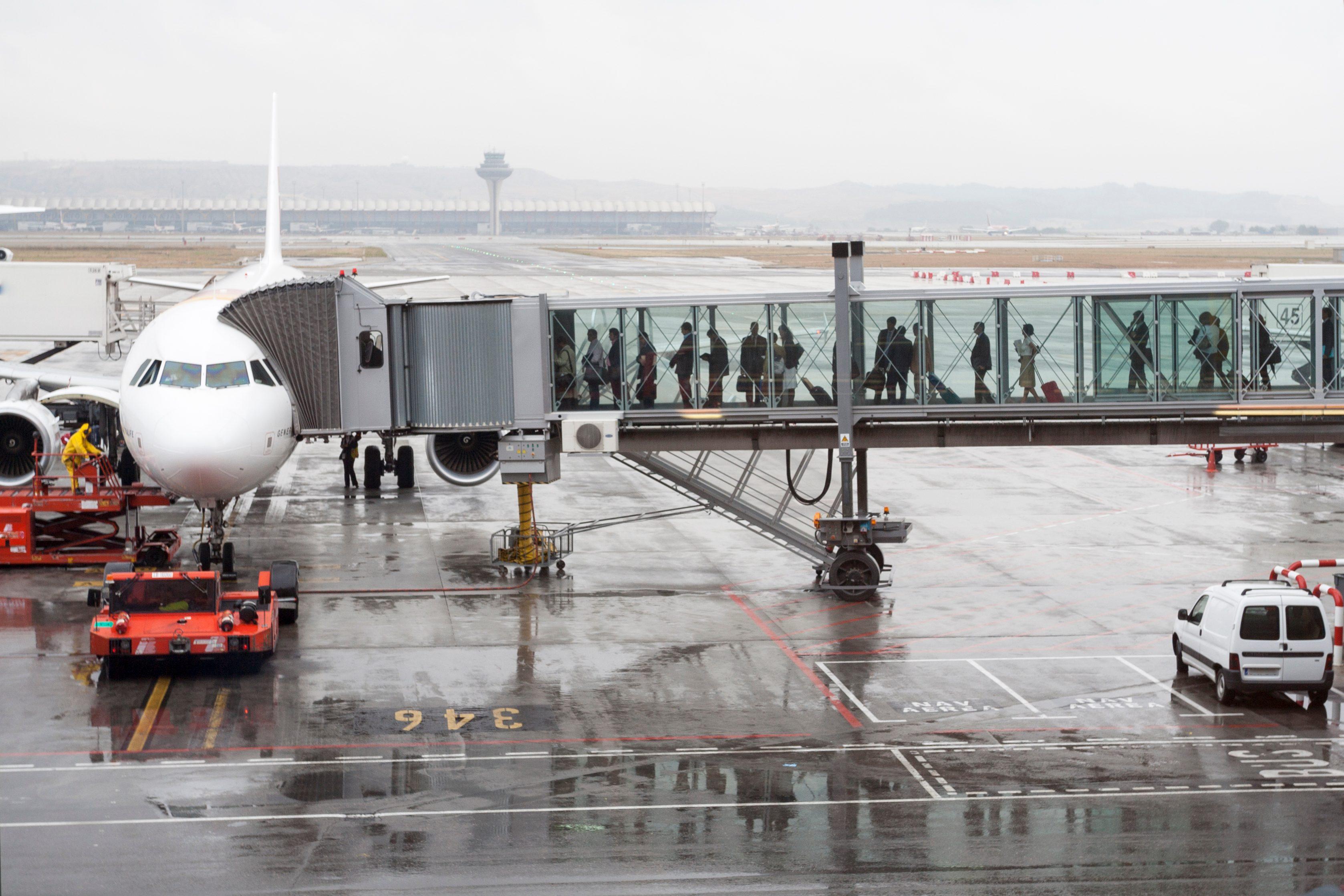 Passengers boarding an airplane through a boarding bridge