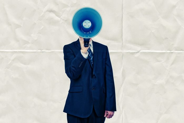 Man holding megaphone in front of face on paper background
