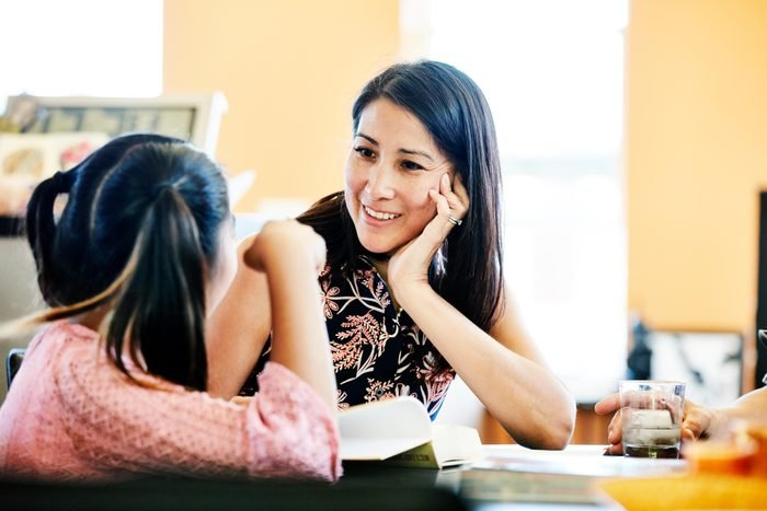 Smiling mother in discussion with daughter while doing homework in kitchen