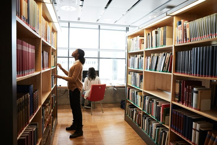 Full length of woman searching book on shelf while friend using computer in university library