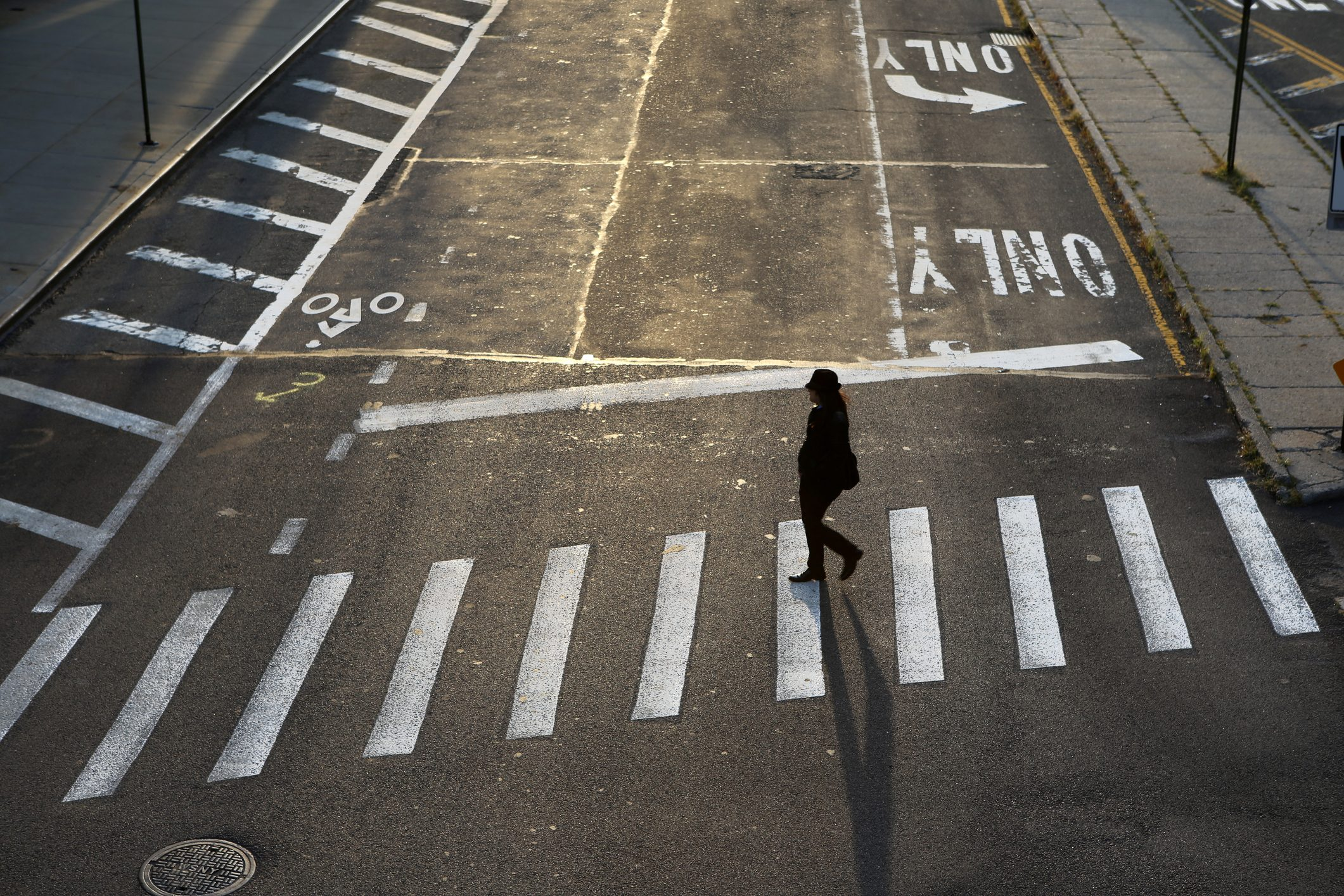 A woman crossing a street in Dumbo, Brooklyn, New York City, USA