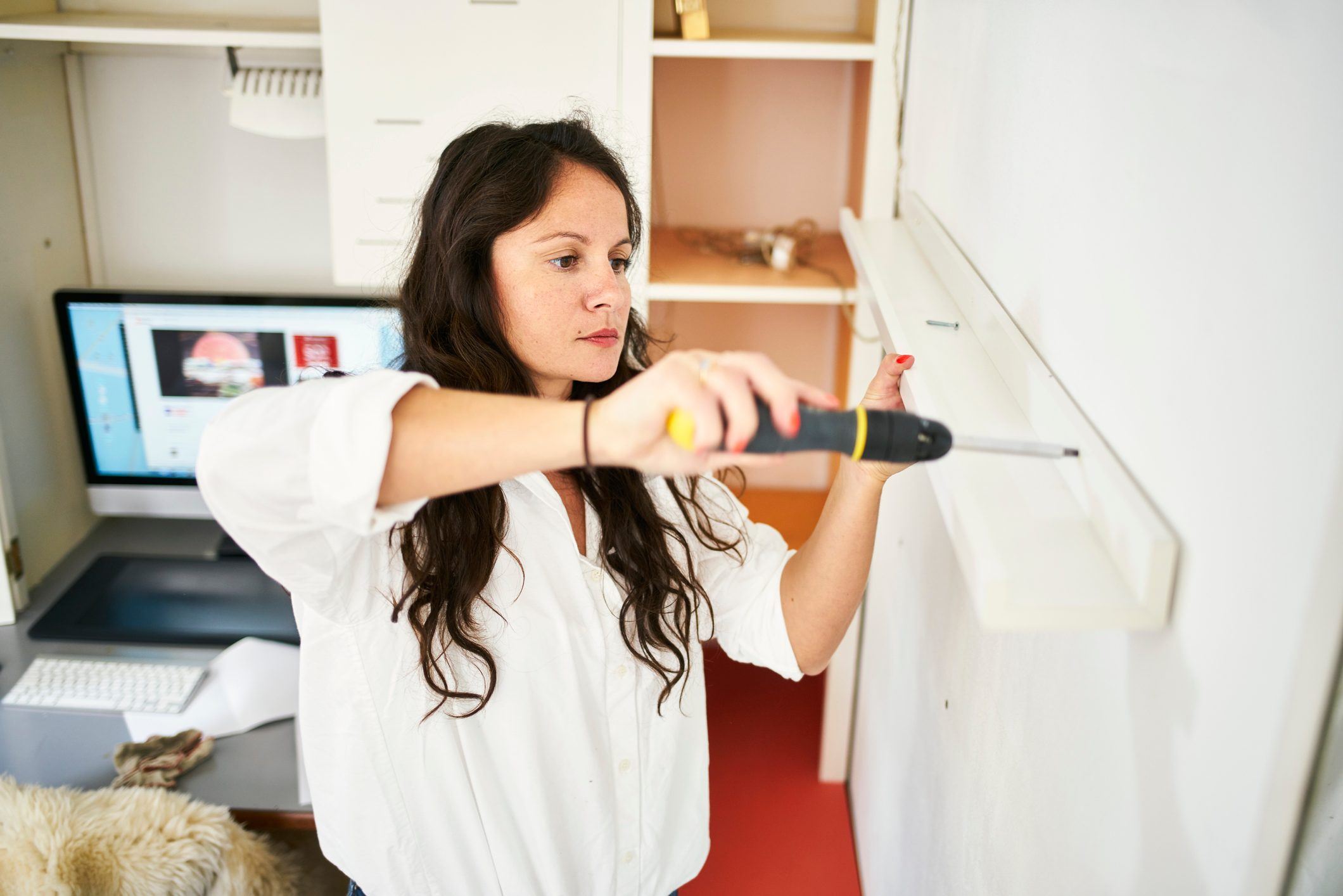 woman fixing a shelf at home with a screwdriver