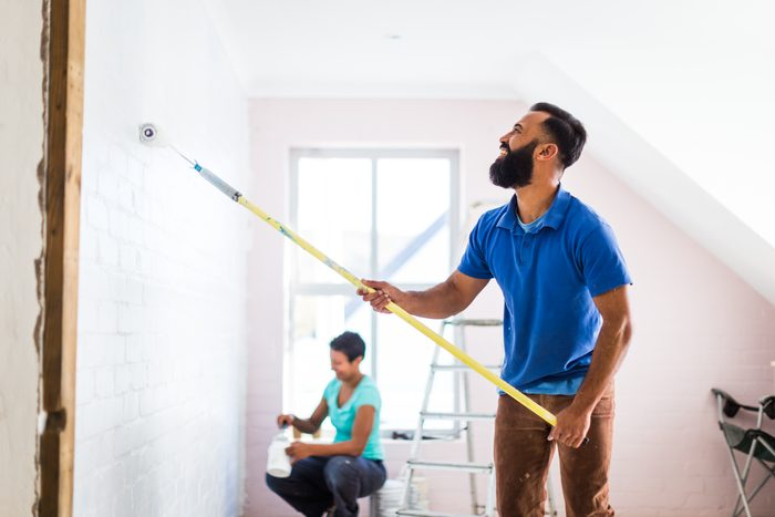 Young mixed race couple painting their home