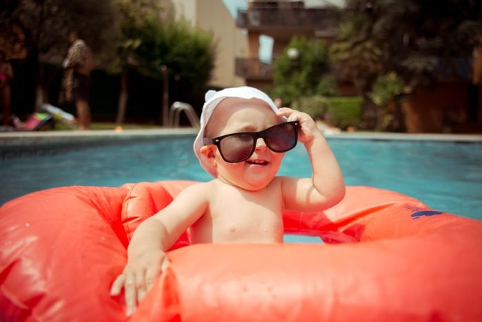 Baby boy wearing sunglasses at the pool