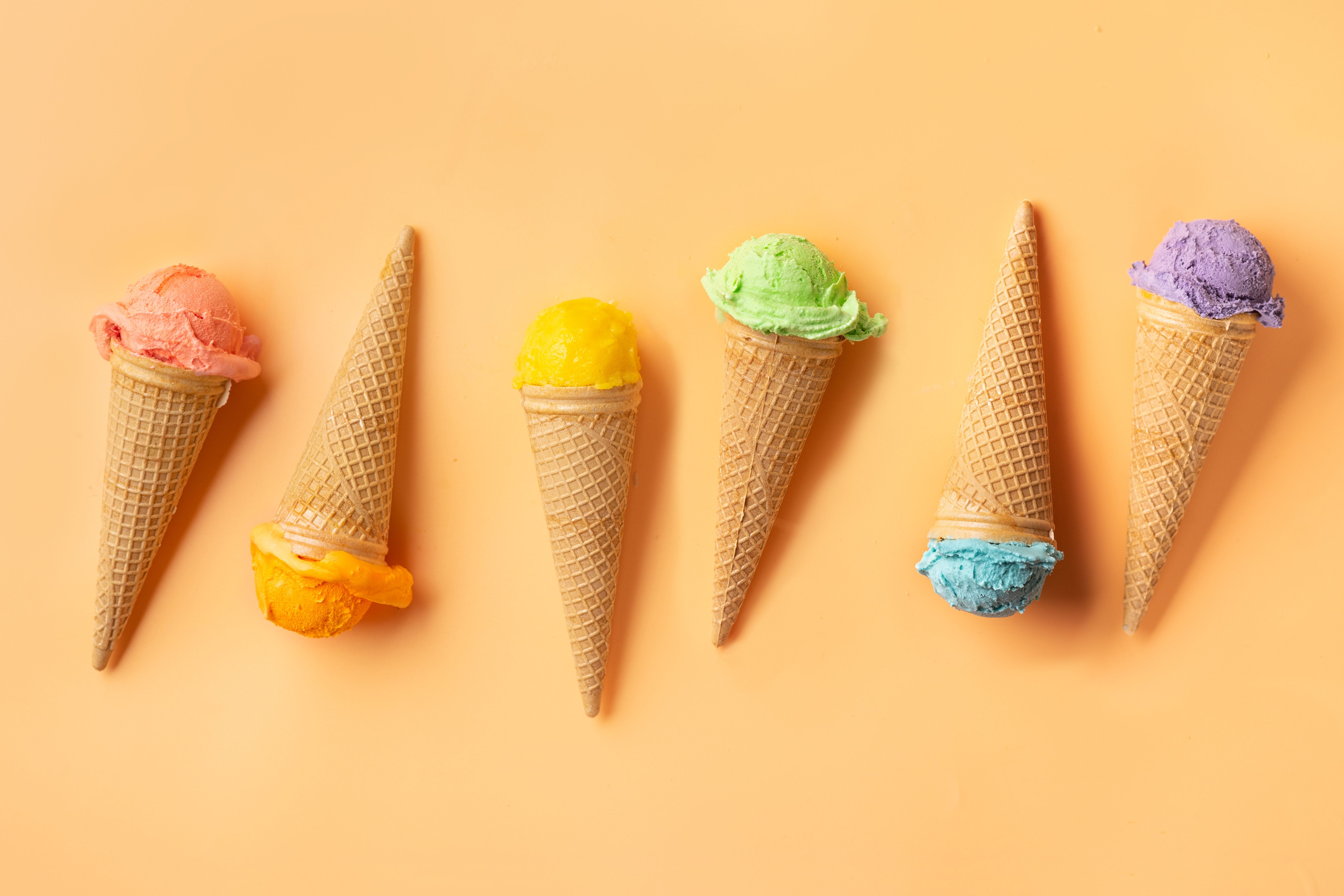 Colorful ice cream cones on yellow backgound. Summer concept