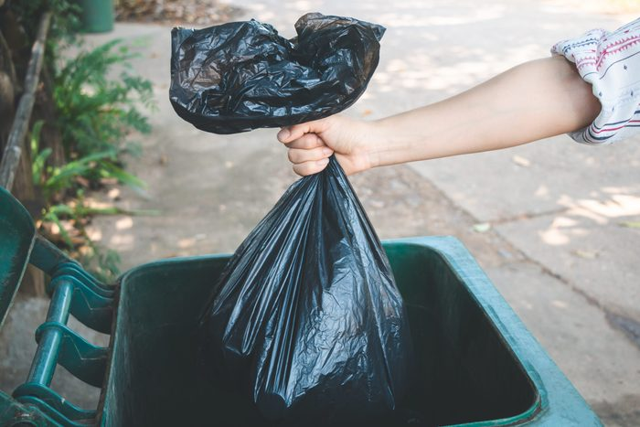 Cropped Hand Of Woman Putting Plastic Bag In Dustbin