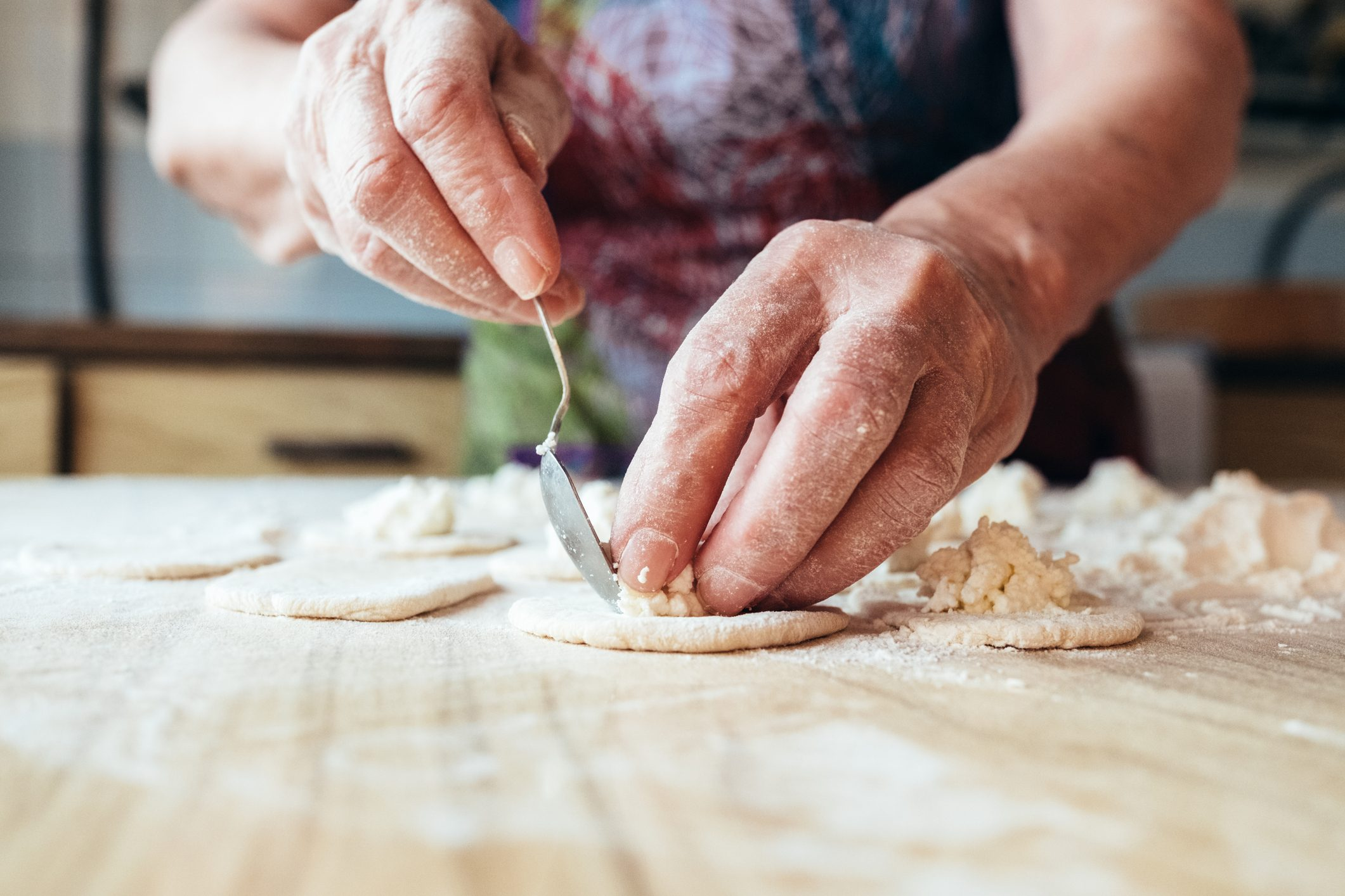 Wrinkled grandmothers hands putting filling in dough. Close up view.