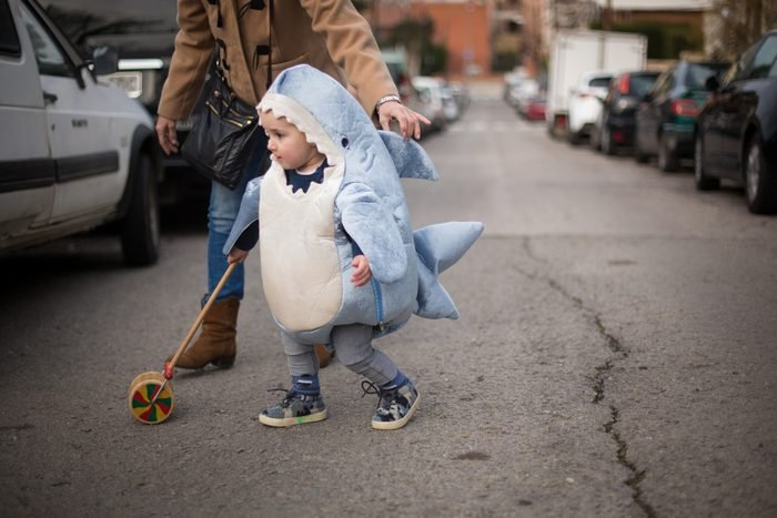 Toddler dressed as a shark crossing the road with grandma