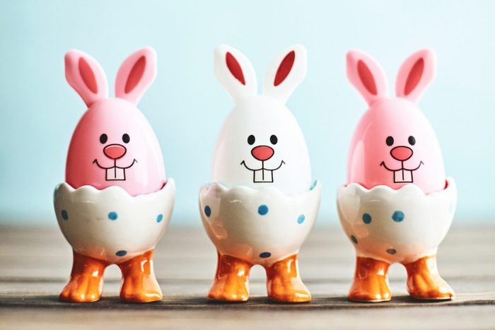 Cute Easter bunny trio in eggcups with blue background