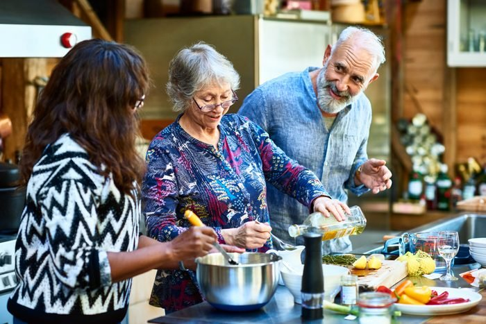 Senior woman making dinner with friends