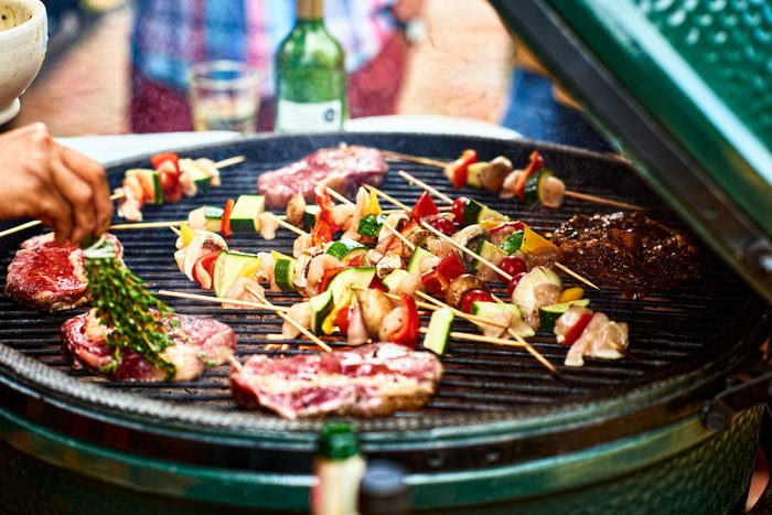 Vegetable skewers and steaks on barbecue