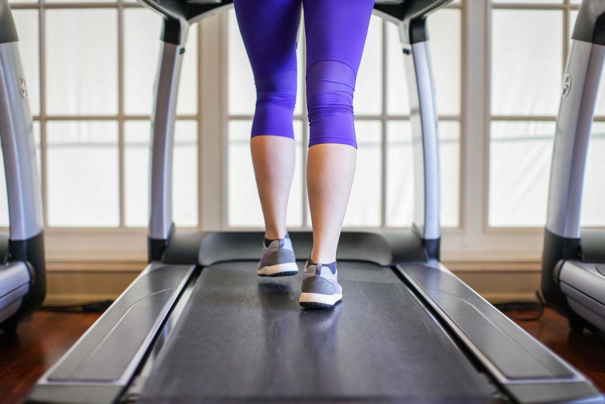 Low Section Of Woman Running On Treadmill At Gym