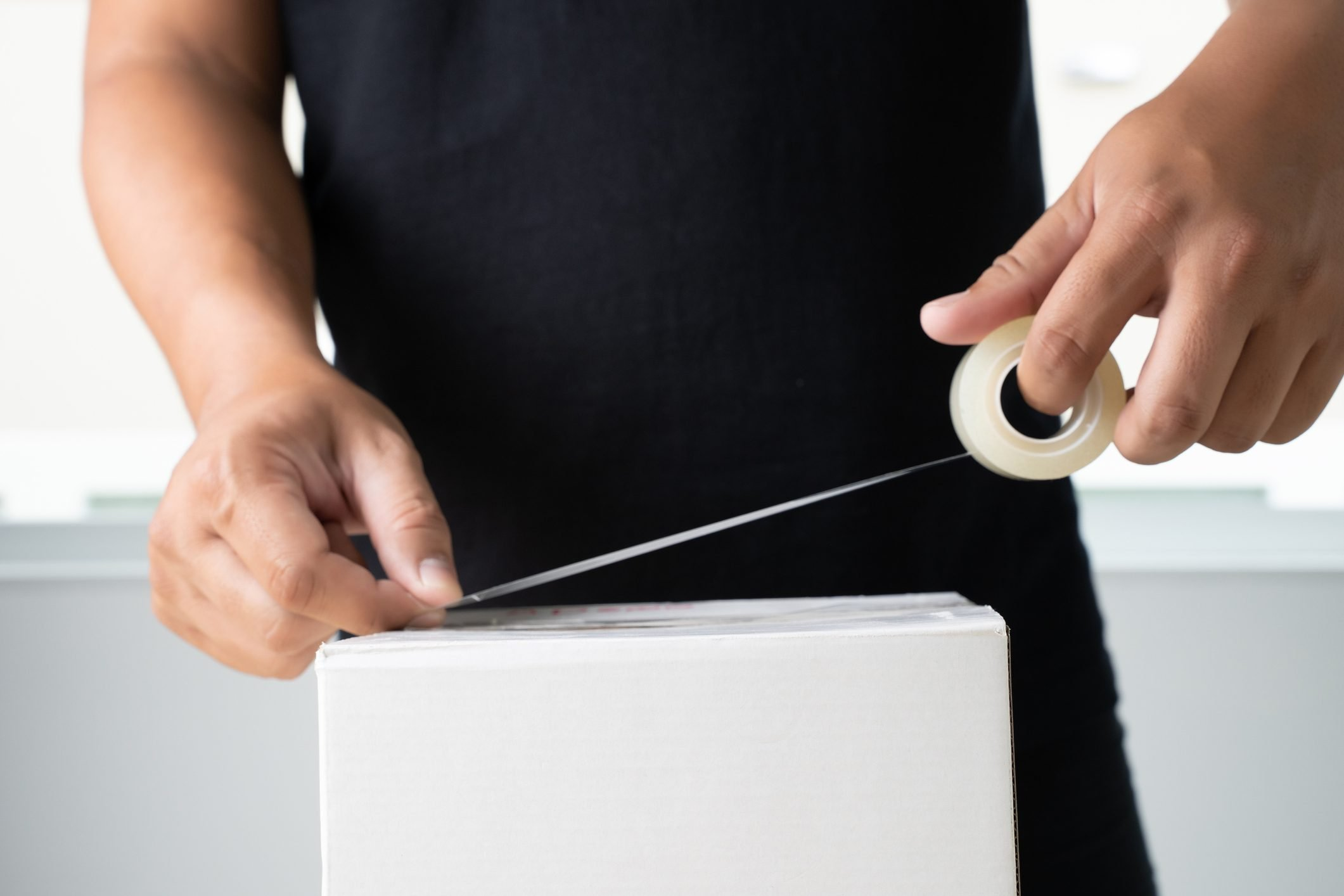 Midsection Of Man Applying Adhesive Tape On White Box At Home