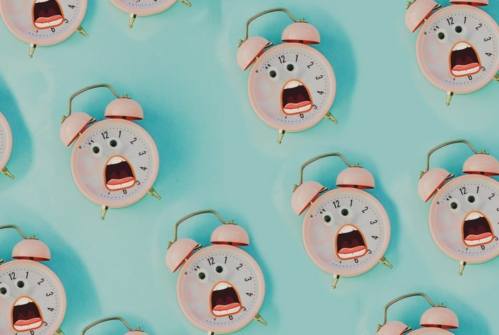 pink alarm clock in pastel colorful background.Top view