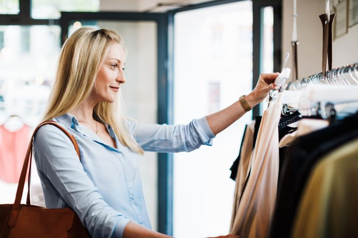 Woman Looking At Dresses On Clothes Rack
