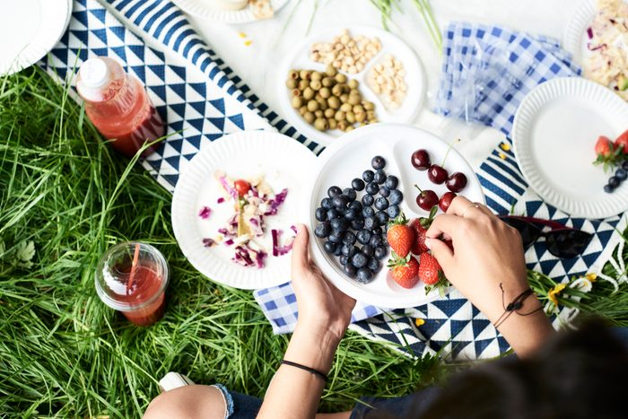 Top view of woman eating berries at a picnic in park