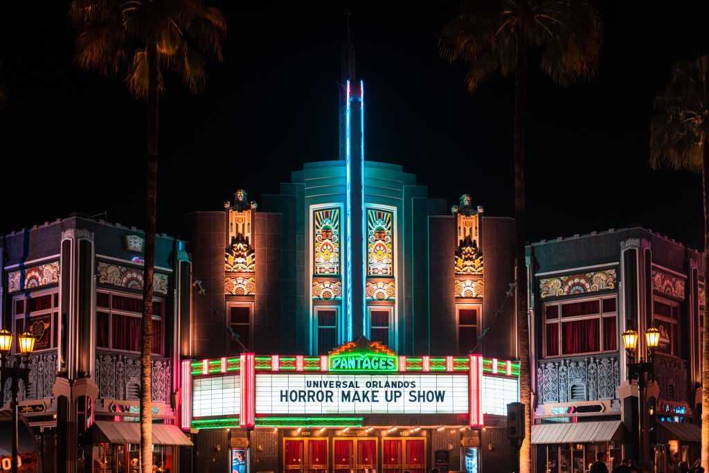 An illuminated movie theater during the nighttime. The scene...
