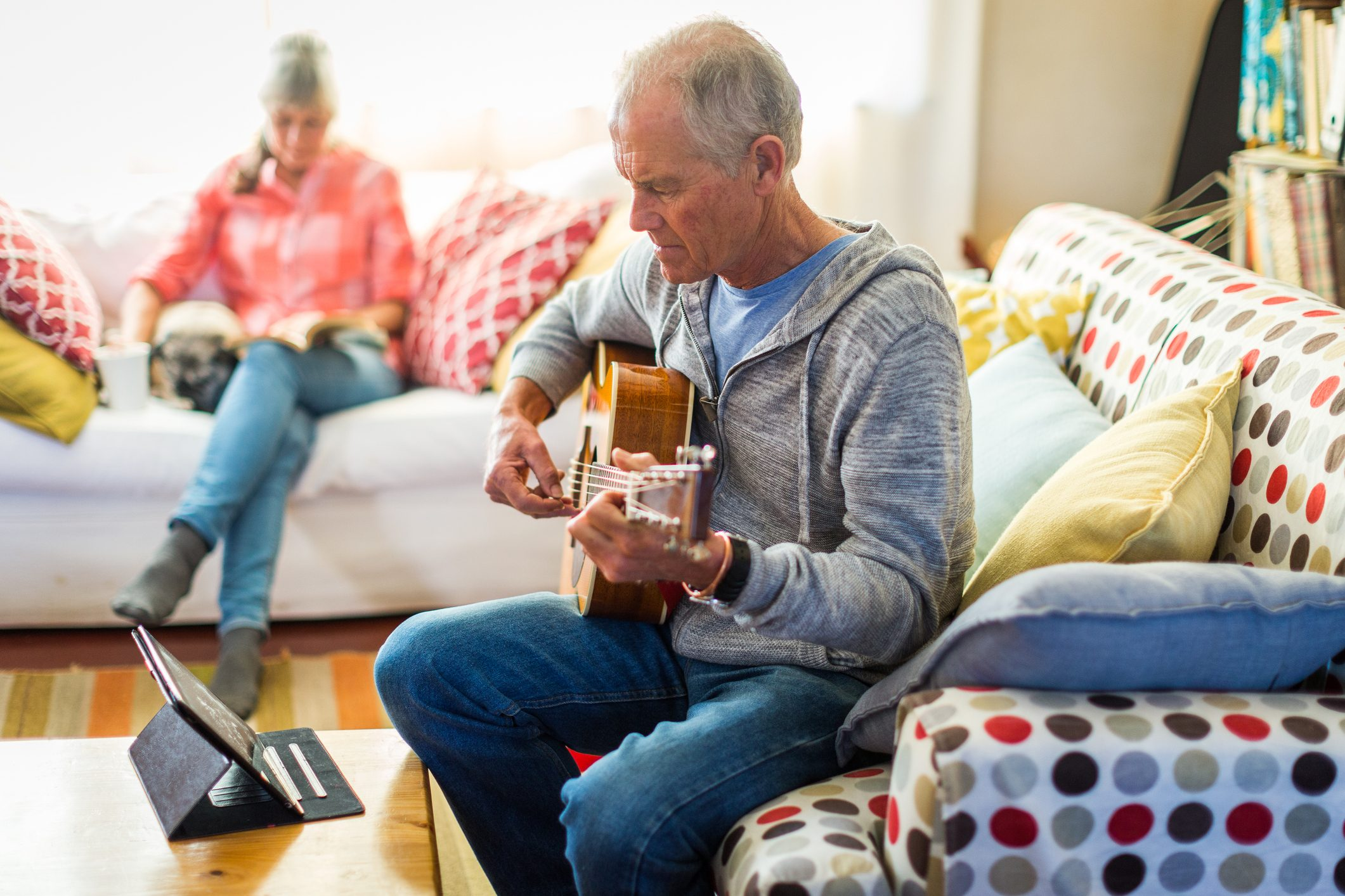 Senior man learning guitar by watching online tutorial