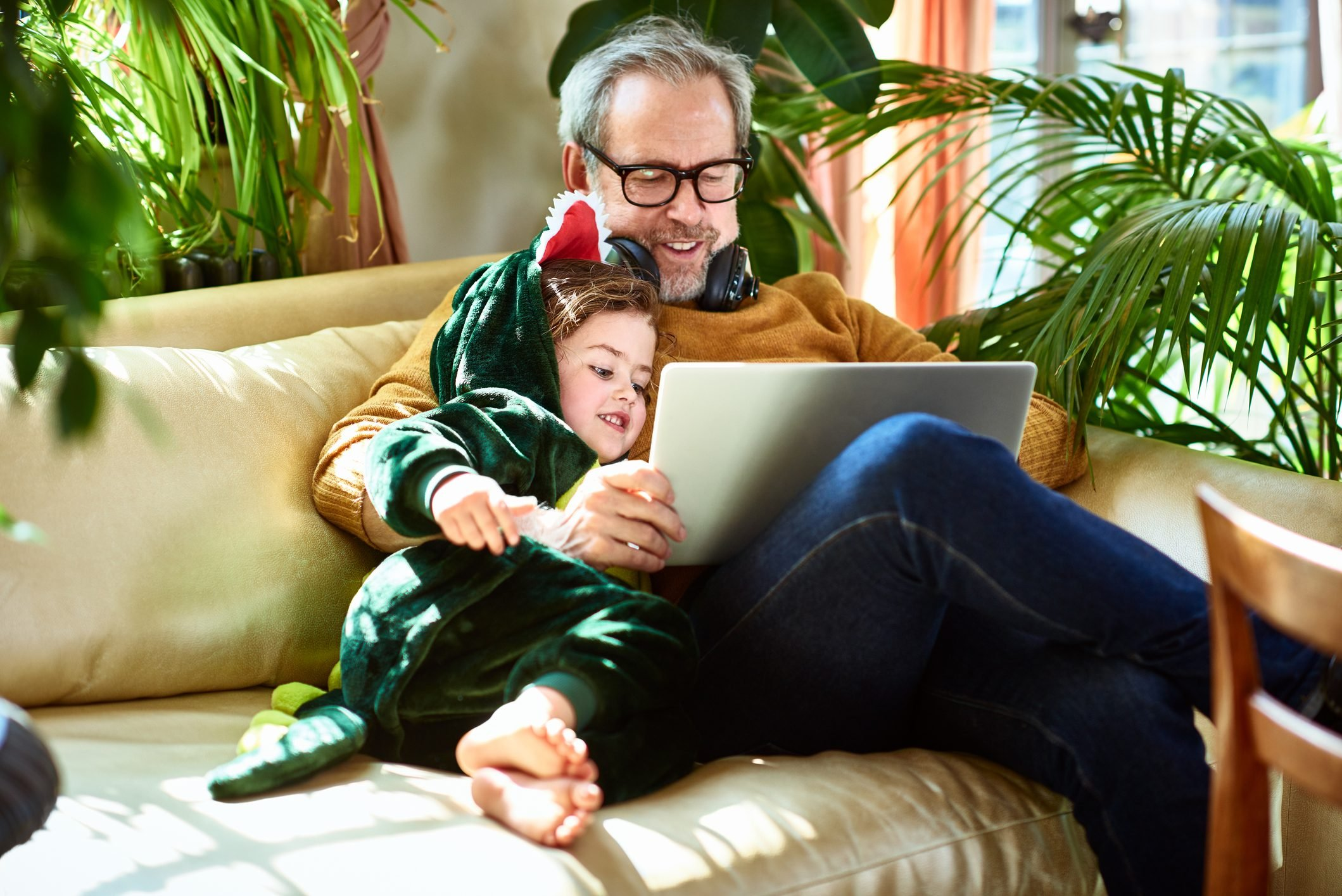 Uncle playing game on laptop with girl in dinosaur outfit