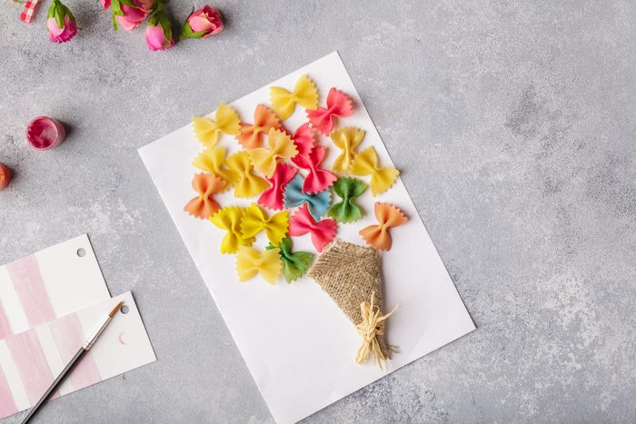 Paper crafts for mother day, 8 march or birthday. Small child doing a bouquet of flowers out of colored paper and colored pasta