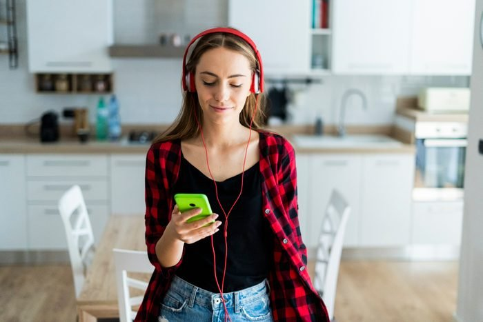 Young woman with cell phone and headphones at home