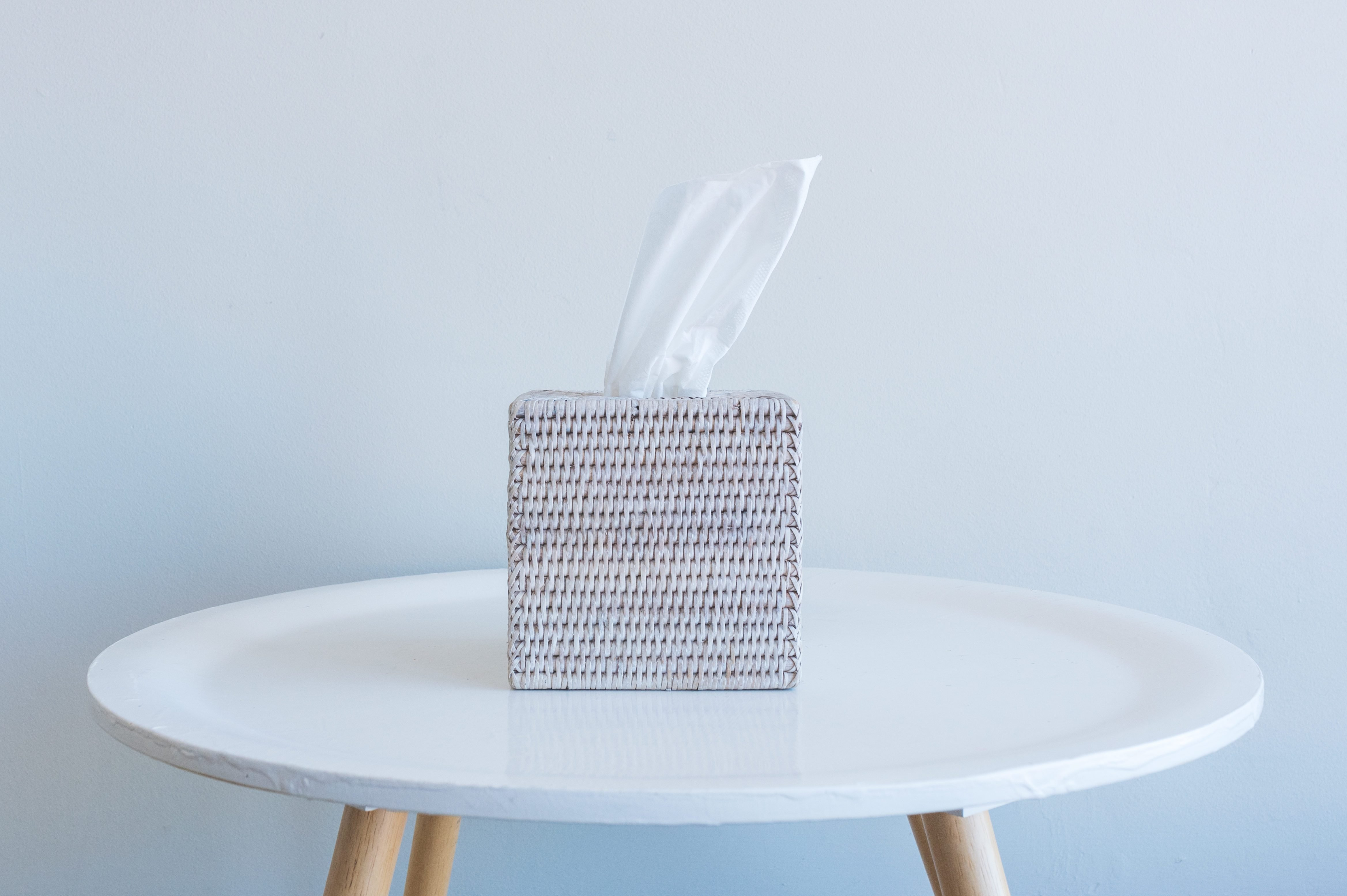 Tissue box on small white table against wall