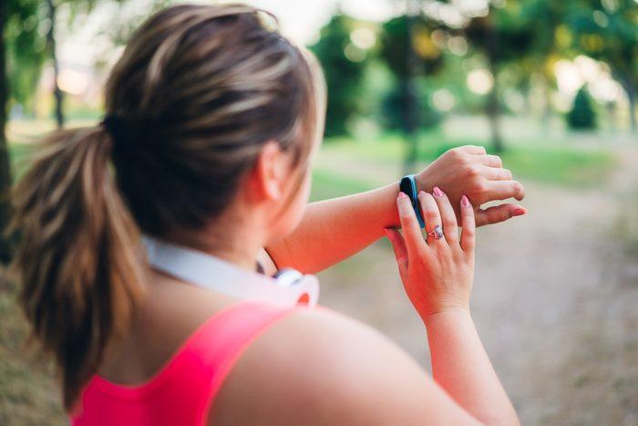 Female overweight runner checking smart watch