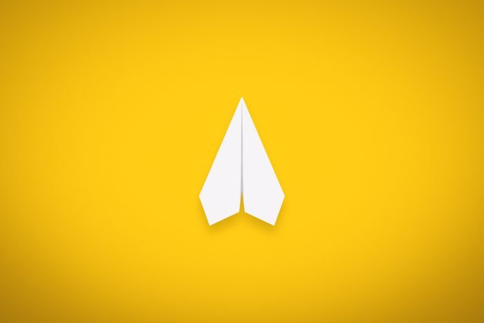 A Single Paper Airplane on Yellow Background