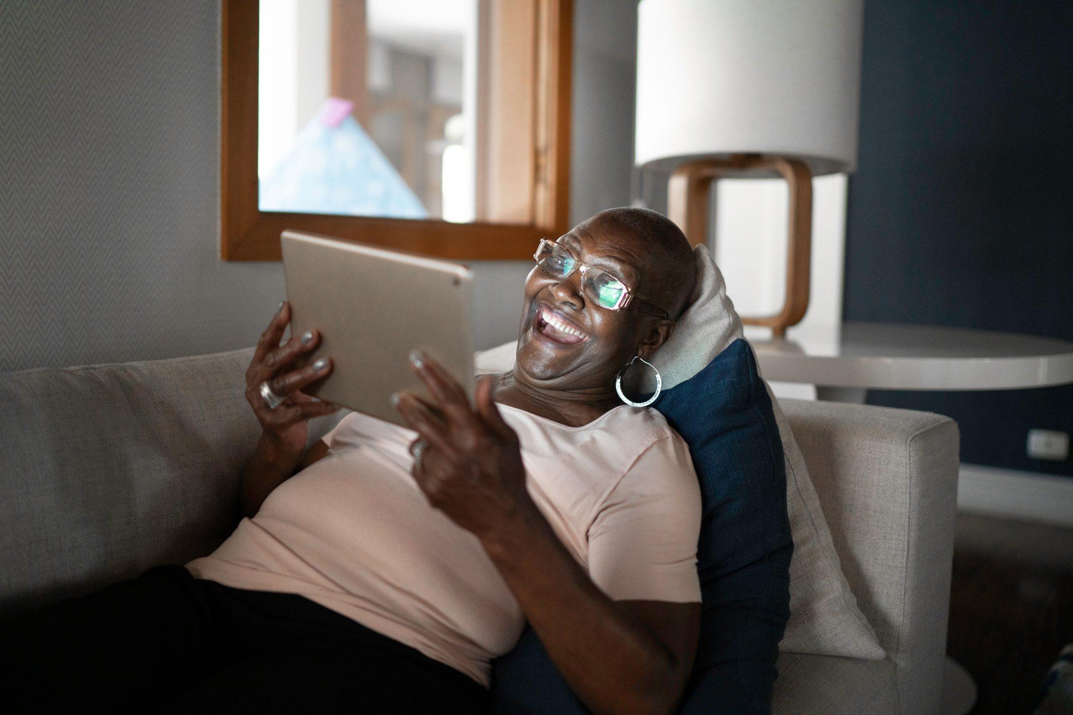 Senior woman lying down on sofa using tablet