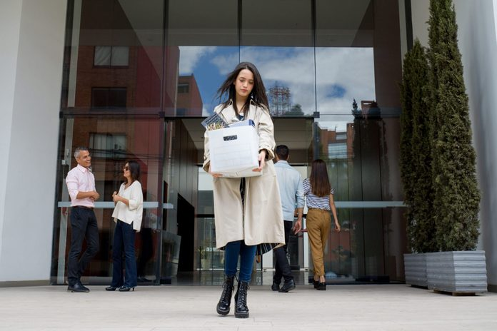 Fired woman leaving the office with her belongings in a box